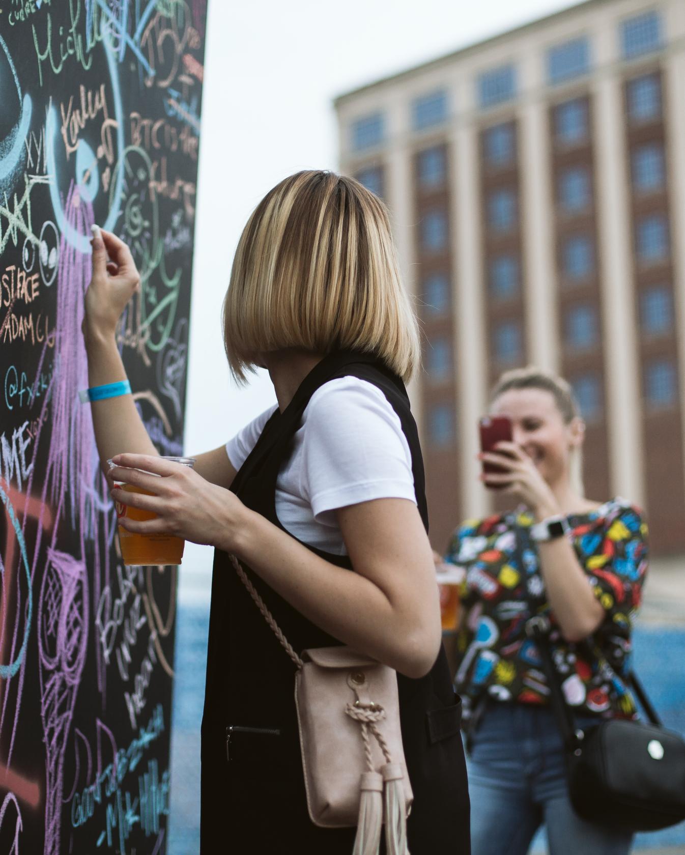 Woman drinking beer while drawing graffiti